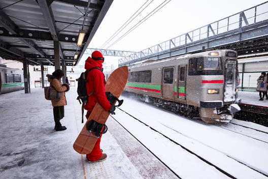 A man taking the train to snowboard