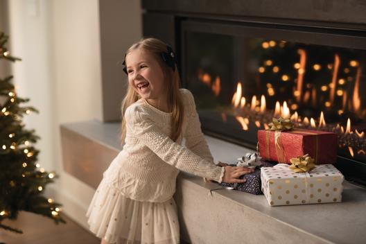 Evening holiday themed portrait of a mischievous young girl inspecting presents on the mantle of a modern, lit fireplace, onto which holiday lights can be reflected.