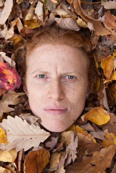 Woman\'S Face Peering Through Autumn Leaves