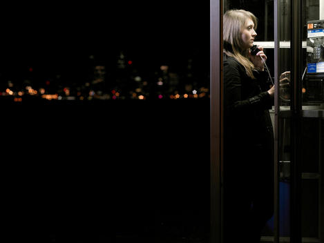 Young Woman In Telephone Booth At Night