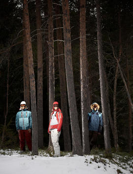 Three Young People Laughing Standing In Snow Between Trees