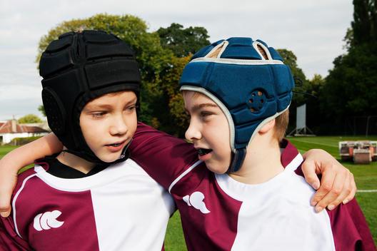 Two teenage schoolboys wearing protective headgear