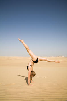 Young Athletic Lady Performing Gymnastics Wearing A Bikini In The Sahara Desert