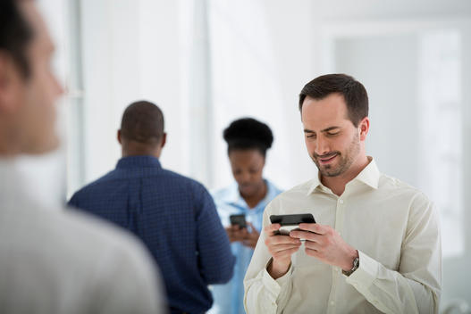 Office Interior. A Group Of People, One Man Using A Smart Phone.