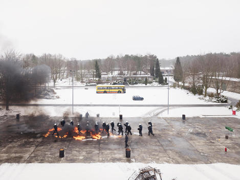 A squad of Riot Police are taught how to deal with fire