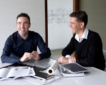 Two Men Sitting At A Table Looking At Plans