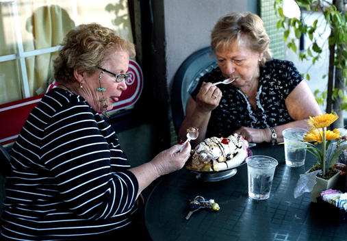 Women sharing summer ice cream banana split sundae