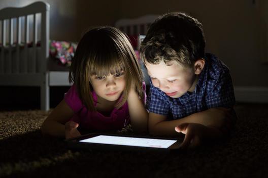 Caucasian children using digital tablet at night