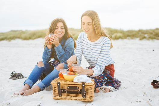 Two young female friends preparing picnic on beach