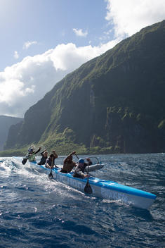 A team of paddlers on an outrigger canoe along the north shore of Molokai