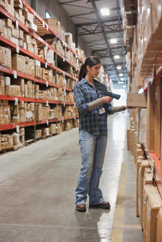 Mixed race woman scanning box in warehouse