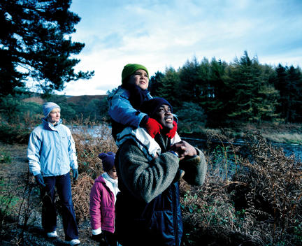 Warmly-Dressed, Young, Mixed-Race Family On Hike By Woods, Codbeck Reservoir