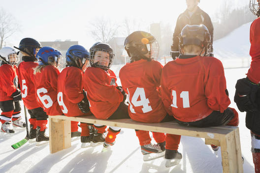 Smiling boy with team on ice hockey rink
