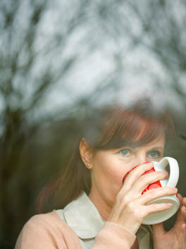 Woman Drinking Coffee behind Window