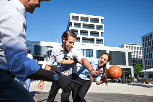 Group of businesspeople playing basketball outdoors