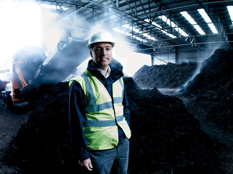 Middle-Aged Man Wearing Reflective Clothing Standing In Warehouse Filled With Large Piles Of Dark, Steaming Compost Material, With Conveyor Machine In Background.