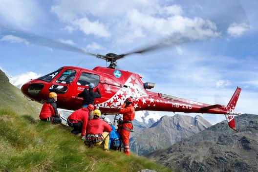 Mountain rescuers are landing with a Air Zermatt helicopter on a grassy slope in the Swiss Alps.