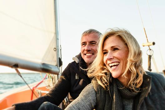 Mature couple on sailing boat, smiling