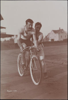 One Man Pushing Another On A Bicycle On A Track At The Bayonne Athletic Club.