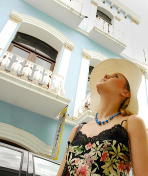 woman (tourist) with white hat watching old colonial colorful buildings