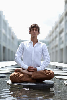 Germany, Bavaria, Young business man relaxing with yoga