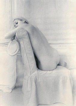 Seated nude woman on covered white chair gazing over her left shoulder and holding a mirror in her right hand