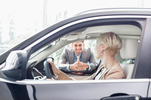 Car dealer with client sitting in new car