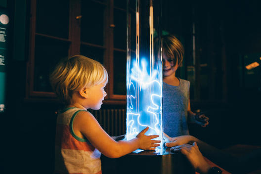 2 year old blonde boy and 6 year old boy playing with blue electric current at the Berlin Museum of Technology.