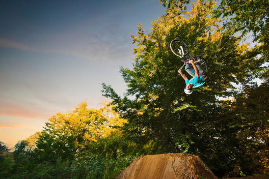 BMX rider performing upside down stunt mid air