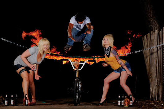 Man doing a BMX stunt which involves jumping over a flaming chain, Austin, Texas, USA.