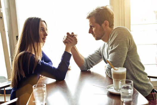 young couple arm wrestling in a cafe