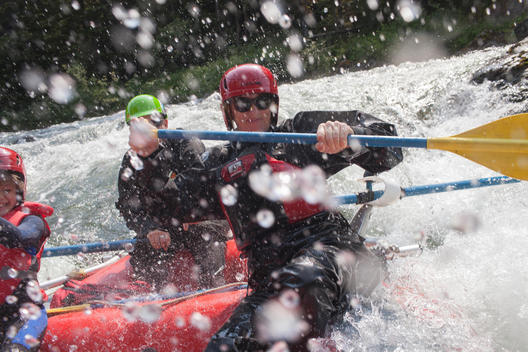 three people getting wet on a white water raft at Clayoquot Wilderness Resort