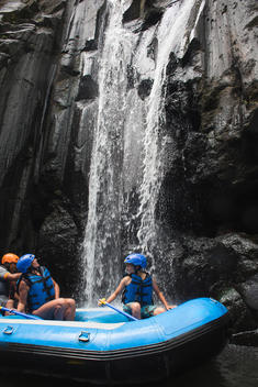 people on a white water raft getting wet under a waterfall along the Ayung river