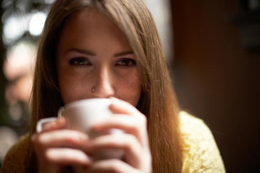 Woman Drinking Coffee In Café