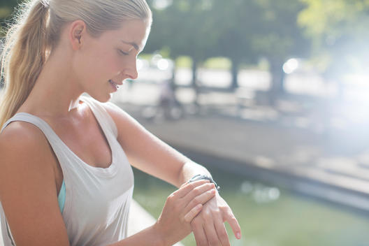 Woman looking at watch before exercising on city street