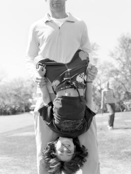A Father Holds His Son Upside Down.