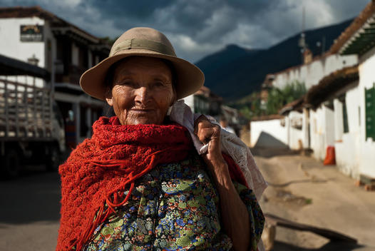 portrait of smiling old woman with traditional hats and scarf, colonial houses in the background