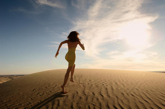 Naked athletic young girl running up a sand dune against a blue sunset sky