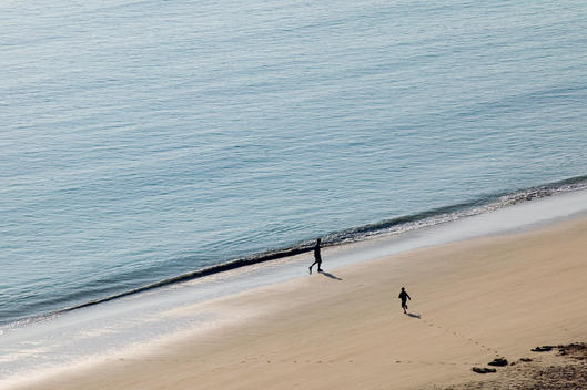 A father and son walk together on Porthminster Beach early one summer\'s morning.