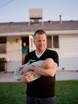 A middle-aged father lovingly cradles his newborn son in the backyard of his family\'s suburban home in late afternoon setting sun with his wife standing in the home doorway in background. Denver, Colorado