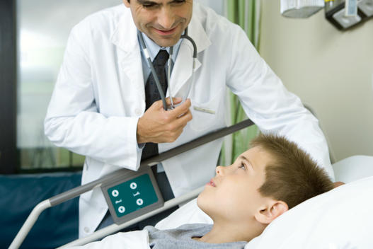 Doctor talking with boy lying in hospital bed