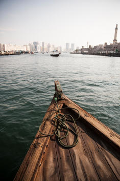 Front of wooden boat on water near city buildings