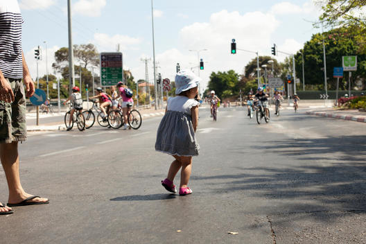 Young Girl On The Road With Her Father, Kids On Bicycles In The Background