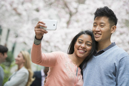 City life in spring. Young people outdoors in a city park. A couple taking a self portrait or selfy with a smart phone.