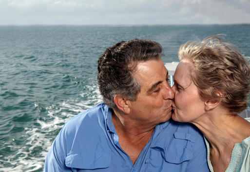 Senior Couple Kissing On Motorboat