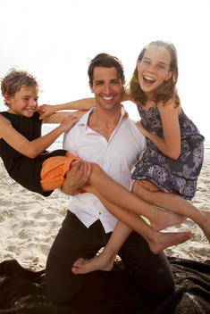 Father Having Fun With Son And Daughter At Beach