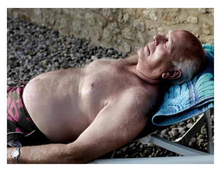 Overweight Senior Man Of Caucasian Appearance Sunbathing On A Deck Chair.