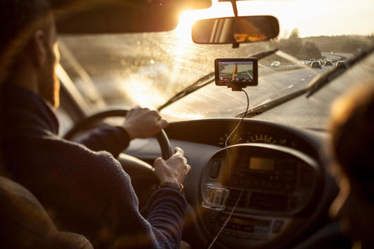 Cropped image of man driving car while using GPS by daughter