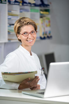 Germany, Portrait of mid adult woman with medical records and laptop, smiling