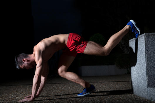 Athletic young man exercising at night, stretching